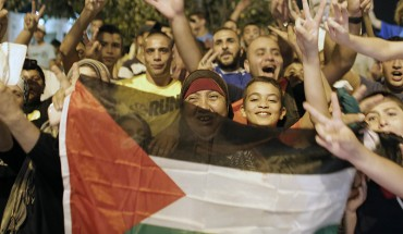 Palestinians flash the sign of victory wave a national flag as they celebrate in the streets in East Jerusalem the long-term truce agreed between Israel and the Palestinians.